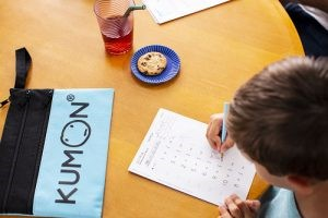 Student doing homework on a kitchen table with kumon pencil case.